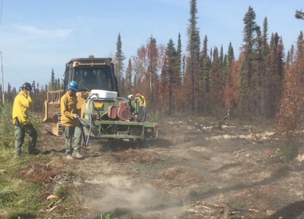 Fire personnel use a hydro-seeder to reseed the dozer line constructed to keep the fire north of Sterling, In the distance the fire backs slowly down the face of Mystery Hills as hot and dry weather increase fire activity on the east side of the fire.