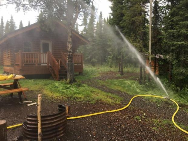 A sprinkler system in use to protect a cabin on the Swan Lake Fire.