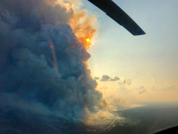 August 26 - View from a helicopter in early evening, column of smoke from burnout operation is visible to the left of the photos.
