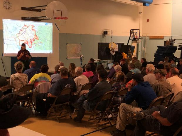 August 28 - A school gym is filled with community members sitting in chairs. A member of the incident management team stands at the front of the room with a map projected behind them.  Community meeting for August 28 in Cooper Landing.