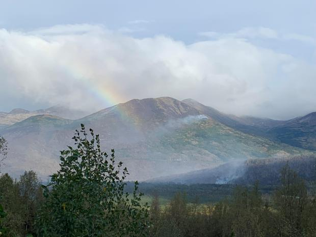 View of Bear Mountain with a rainbow on the left side and smoke visible
