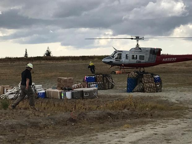 Helicopter flying and landing supplies from fireline