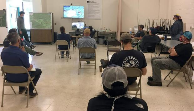 Members of the AK Incident Management Team's Command and General Staff and Agency Administrators sitting in a socially distanced manner while at a Planning Meeting on June 13, 2020, on the Isom Creek Fire in the school, serving as Incident Command Post.