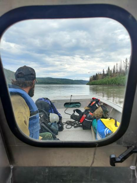 View through a boat console with a Pioneer Peak firefighter wearing a blue life jacket, looking away toward the Yukon River flowing around the boat.
