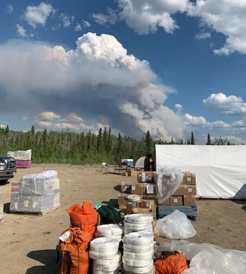 A white column of smoke rises in the distance, viewed from  the area around the supply tent where organized piles of equipment sit, at the Forward Operating Base  for the Isom Creek Fire in June, 2020.
