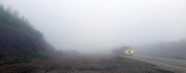 A large truck, barely visible, drives with headlights on up the Dalton Highway through heavy fog. Photo taken in the Yukon River valley on June 20, 2020. The fog moderated Isom Creek Fire (#187) activity.