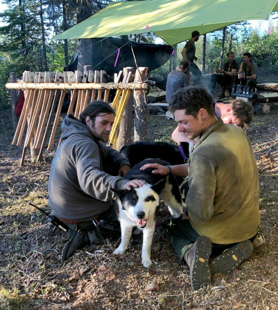 Two firefighters are sitting down petting two black and white Karelian bear dogs with their camp in the background.