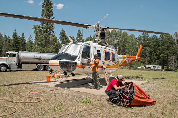 A Helitack helicopter sits on a concrete pad surrounded by pine trees. Three individuals work on different parts of the helicopter. One works on the top, near the propeller, one at the pilot's door, and one on the ground working on the water bucket.
