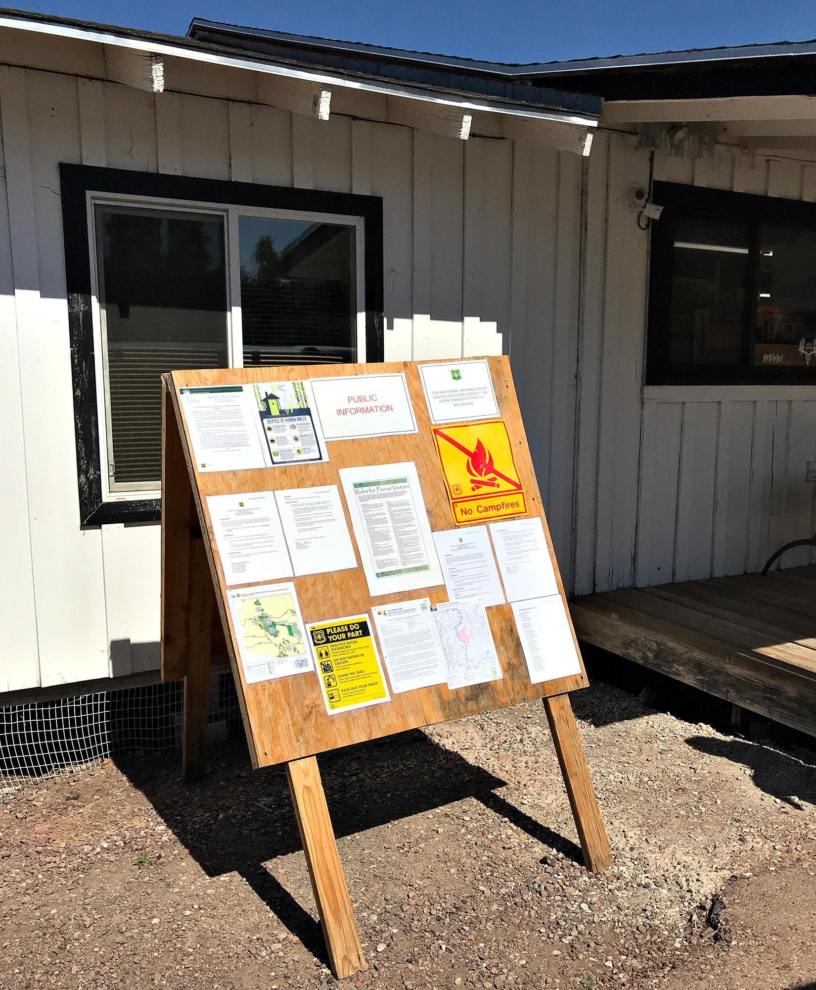 Large wooden slant board with multiple paper fliers. Some flier titles read: Public Information, No Campfires, Rules for Forest Visitors, and Please Do Your Part.