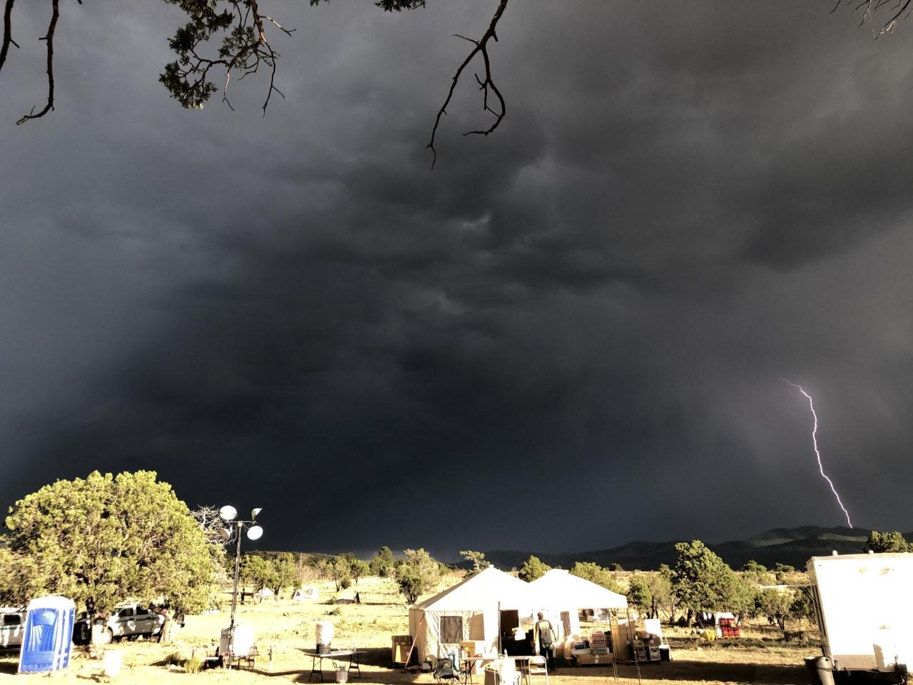 Nighttime photo of fire camp with multiple tents, tables, and chairs. The sky is extremely dark with clouds, lit up by a long single lightning bolt aiming towards the mountains in the background.