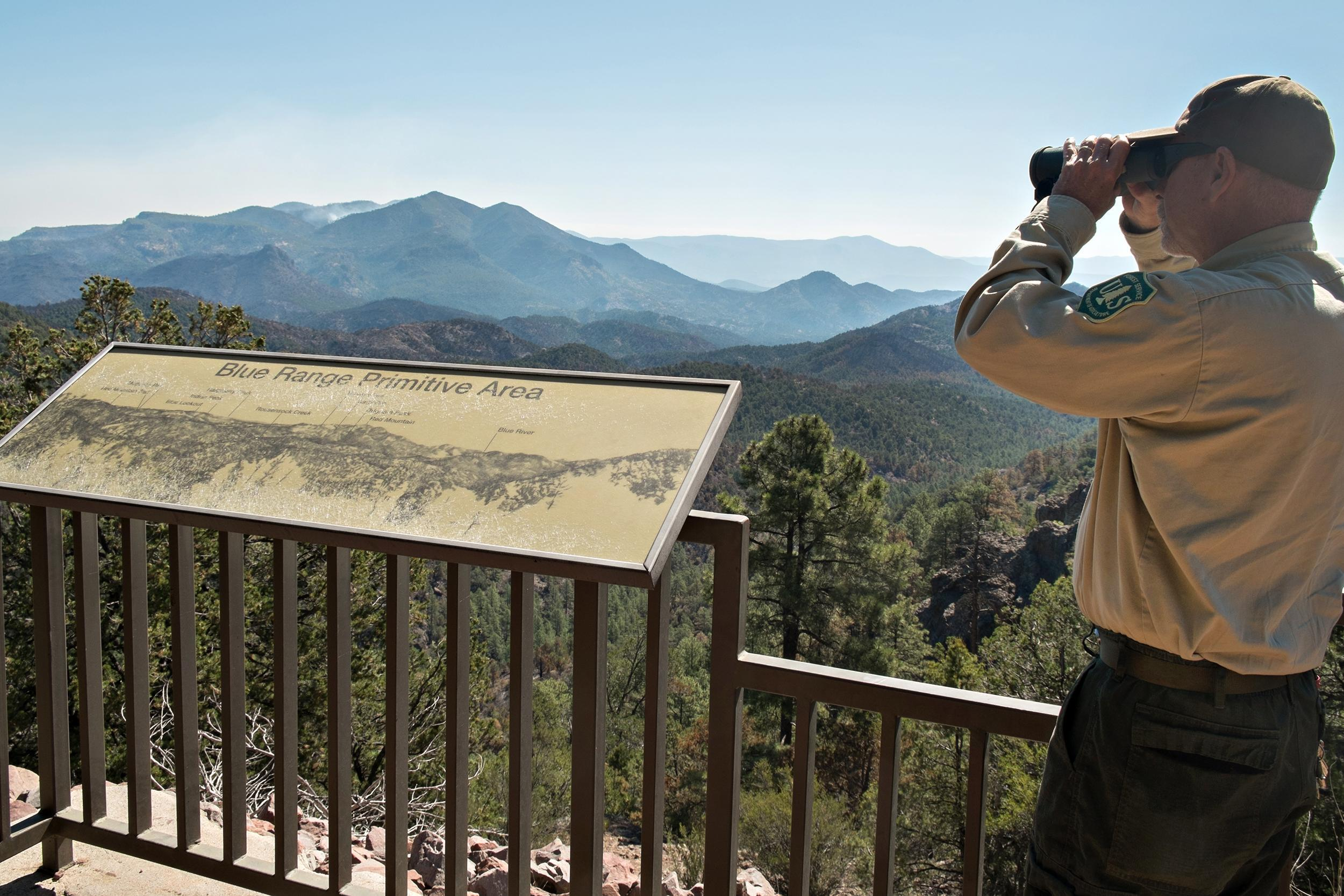 A daytime photo of a person in a Forest Service shirt standing at an outlook spot, looking through binoculars into the distant mountains. The mountains are layered, starting off dark blue, becoming progressively lighter as they fade away.