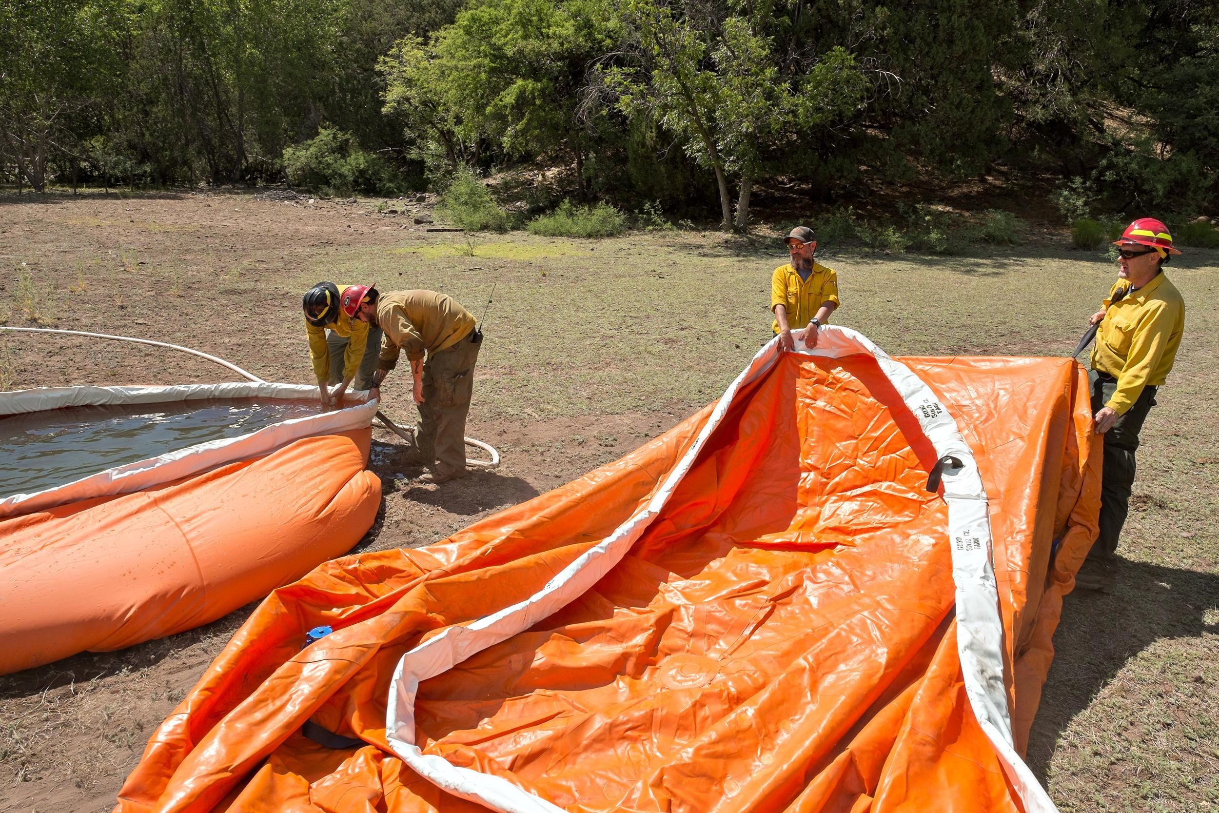 "Four firefighters in yellow shirts and hard hats stand in front of 2 orange ""pumpkins"" water containers. One is empty of water and being moved by two of the firefighters. The other is full of water with 2 firefighters standing above it and reaching in."