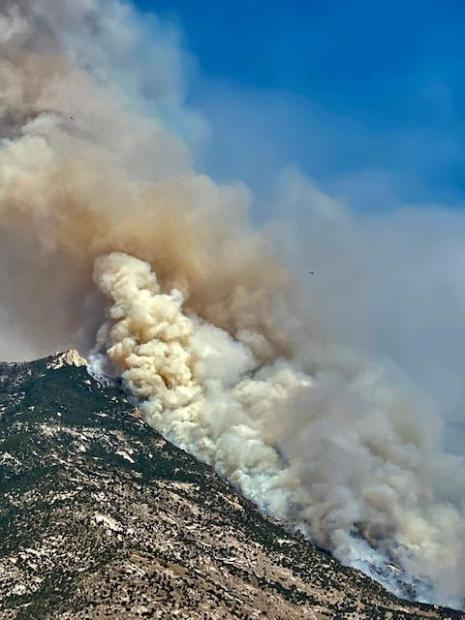 smoke rises from the side of a mountain