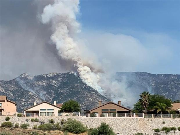 smoke rises on a mountain behind houses
