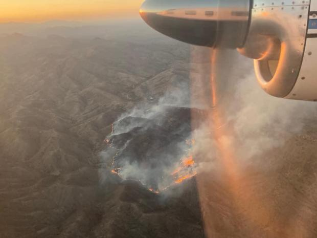 Plane flying over the Warsaw Fire the evening of May 16th.  Flames and smoke can be seen along the fire perimeter and within the interior with the sun setting in the distance.
