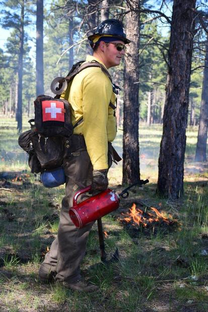 Firefighter lighting specific areas with drip torch.