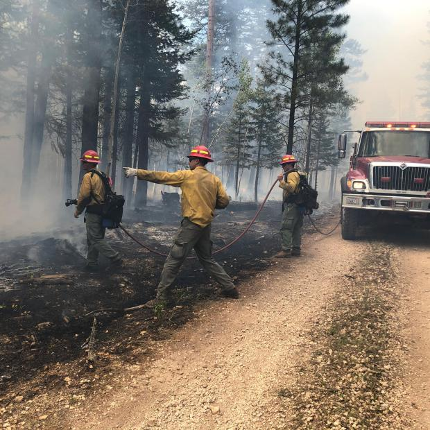 Two firefighters hold a hose while a third firefighter stands between them points towards the distance.