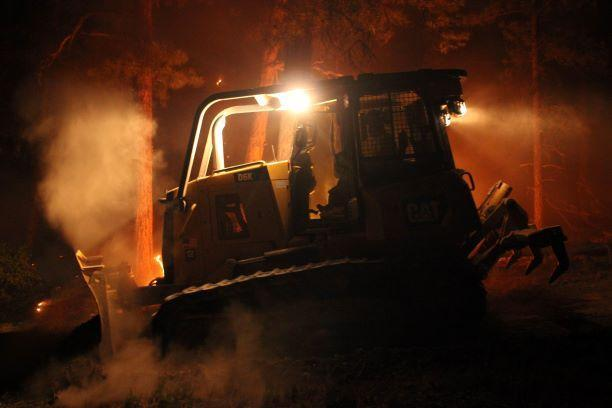 Dozer works among flames in distance night shift
