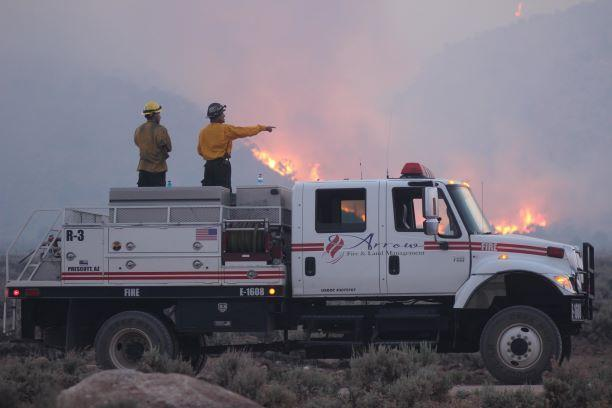 Two firefighters stand on a fire engine overseeing fire ops/photo taken by McCall smokejumper Mike McMillan