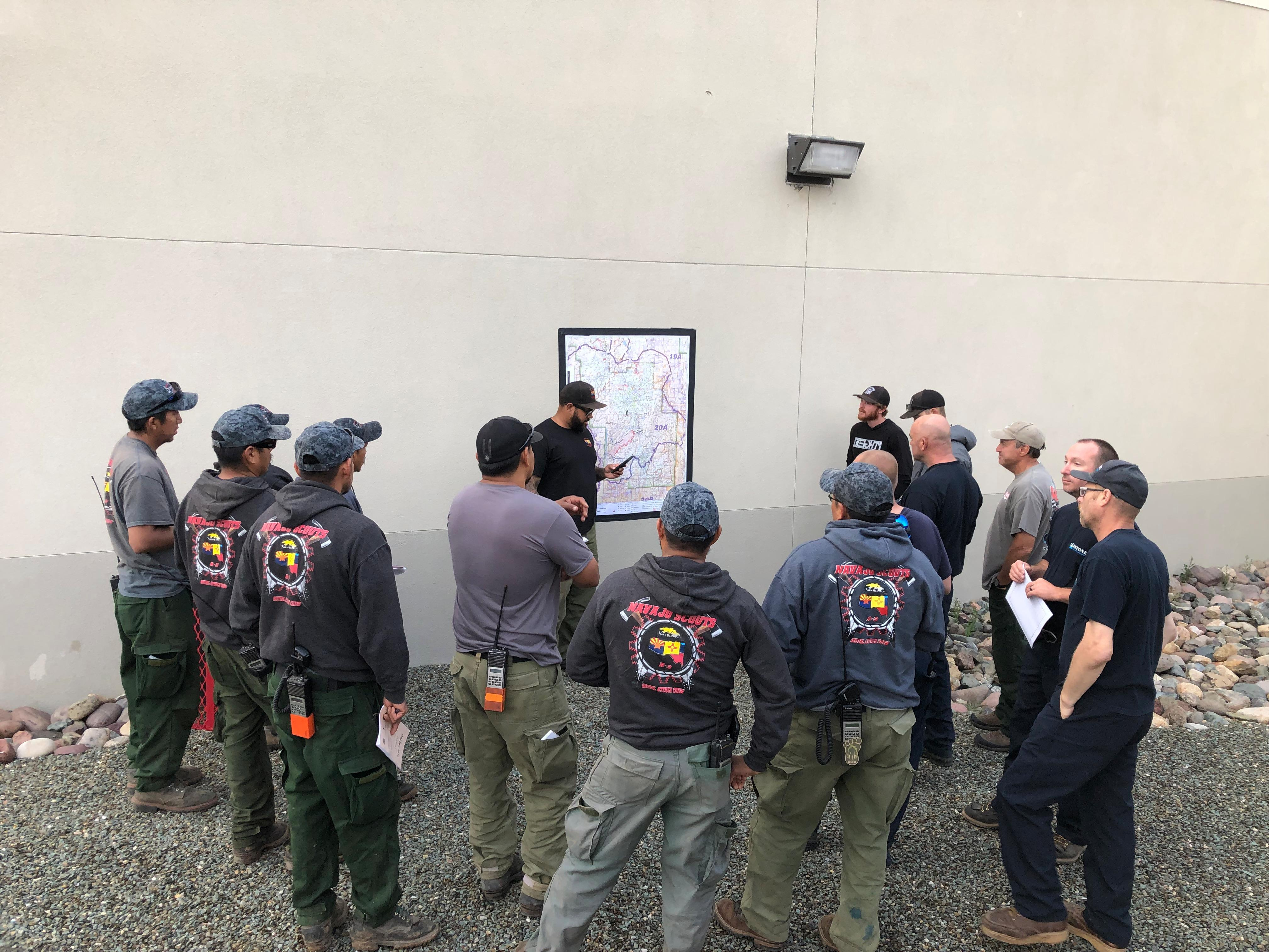 Firefighters meet after morning briefing to discuss their assignment for the day