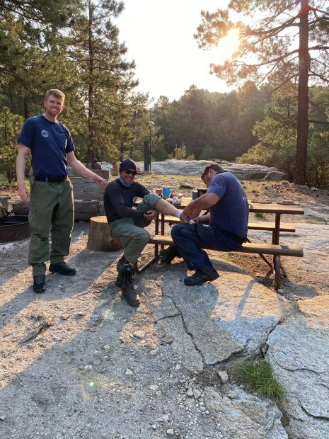 Two men sitting at a picnic table, one is holding the others foot, providing minor first aid.  A third man is standing nearby.  All are smiling.