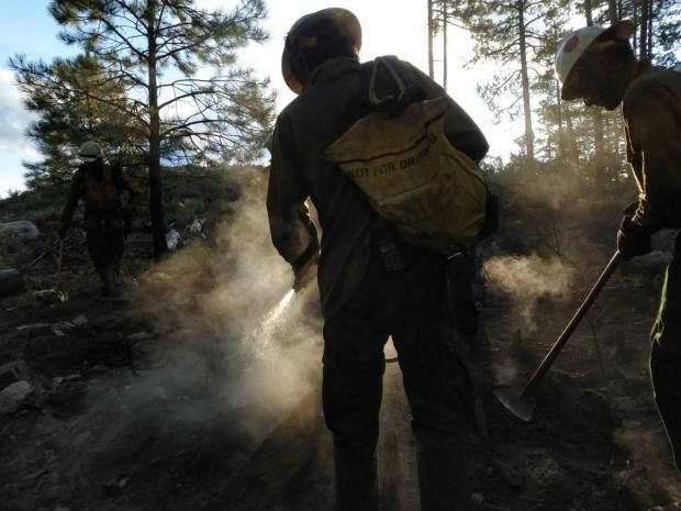 Two firefighters in yellow shirts ad white helments in the foreground spray water from a yellow backpack.  The air is hazy with smoke and ash
