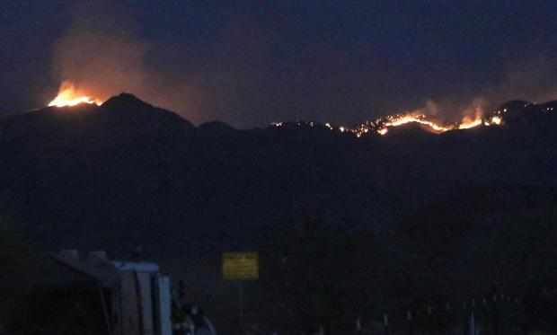 Flames are visible against  dark hills and black night sky