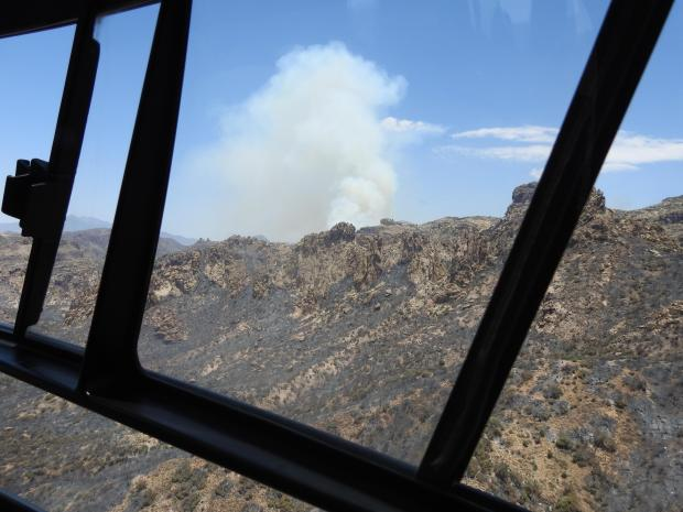 Photograph from a helicopter of a smoke plume that is from an interior pocket burning.