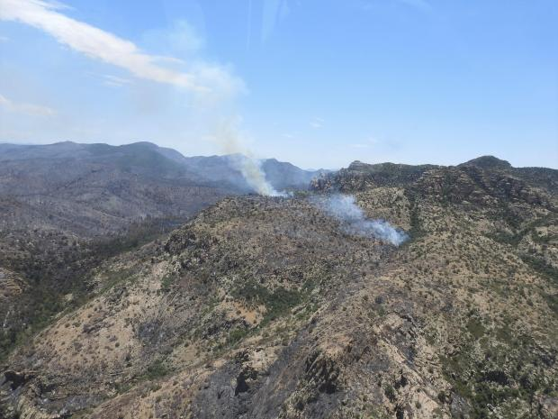 A small smoke plume is visible on the landscape as interior pockets burn in the Rough Canyon area.