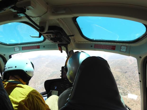 A photograph from the second row of a helicopter with a BAER team scientist sitting next to the pilot. The team takes data and observations from the air as well as on the ground.