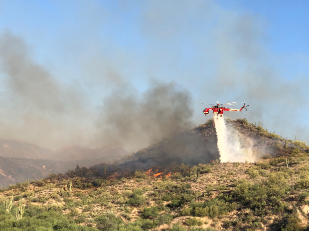Helicopter dropping water along a burning ridgeline.