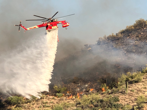 A helicopter drops water on the Bush Fire on June 18, 2020