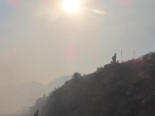 Smoky silhouette of a firefighter on a mountain during a burnout operation in the Oak Flat area on the Telegraph Fire.