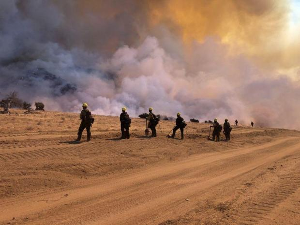 group of firefighters monitor fire