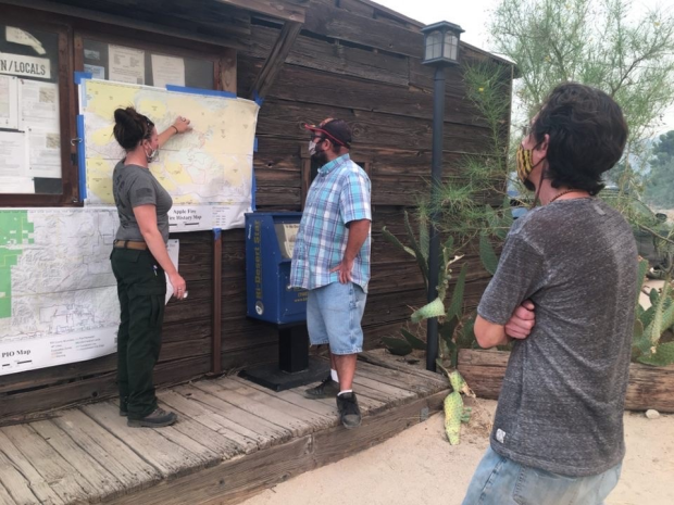 Fire information officer standing in front of map giving updates to public
