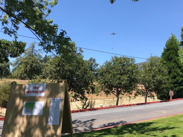 Fire information board with helicopter in background