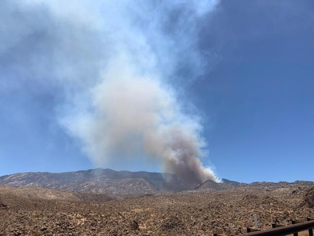 Smoke rises from dry desert slopes covered in chaparral.