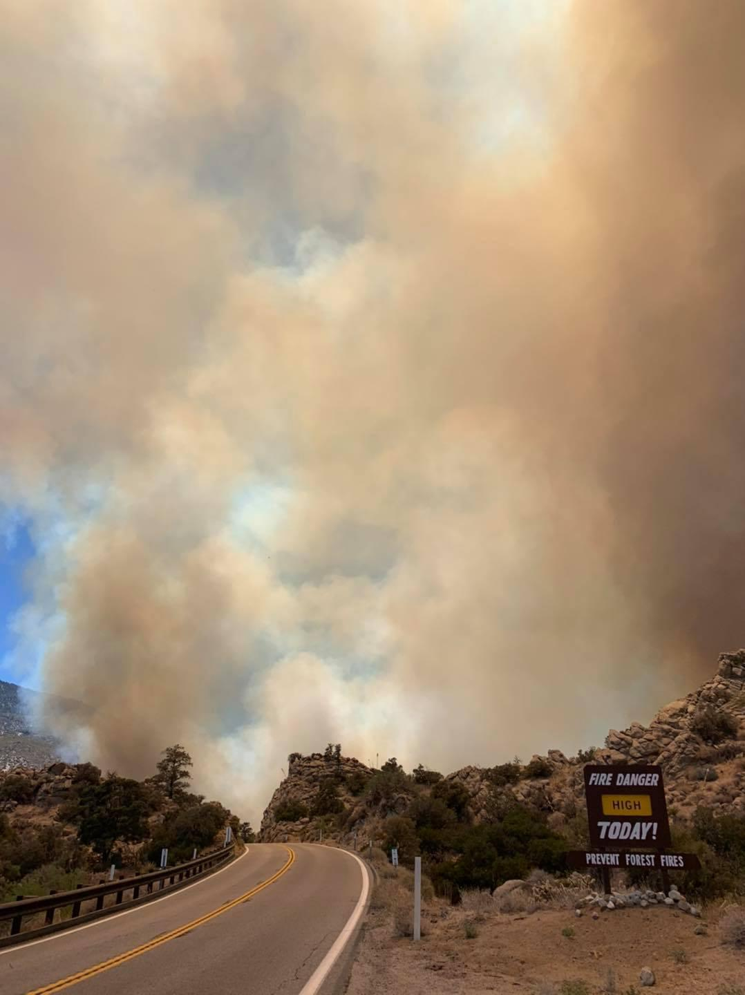Dark smoke rises from behind a hill. In the foreground is a Fire Danger sign that says high.