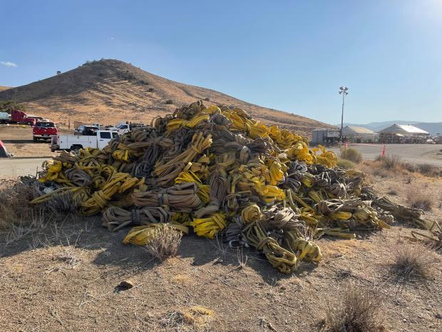A pile of coiled fire hose, no longer needed by demobilizing fire crews, awaits a trip back to the fire cache to be prepared for a future fire. Photo by Charity Berry.