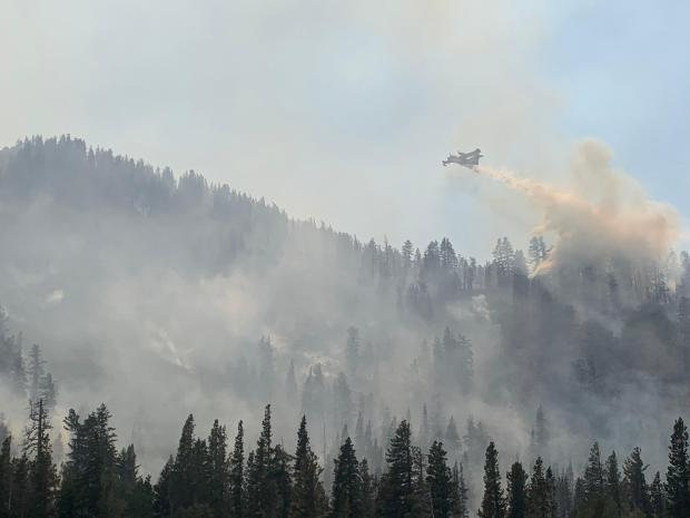 A plane flying over a wildfire dumps water through the smoke.