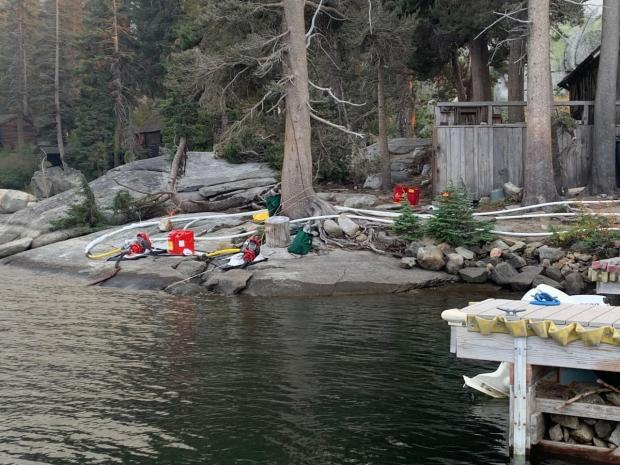 Pumps and hoses are lined up along a rocky lakeshore.