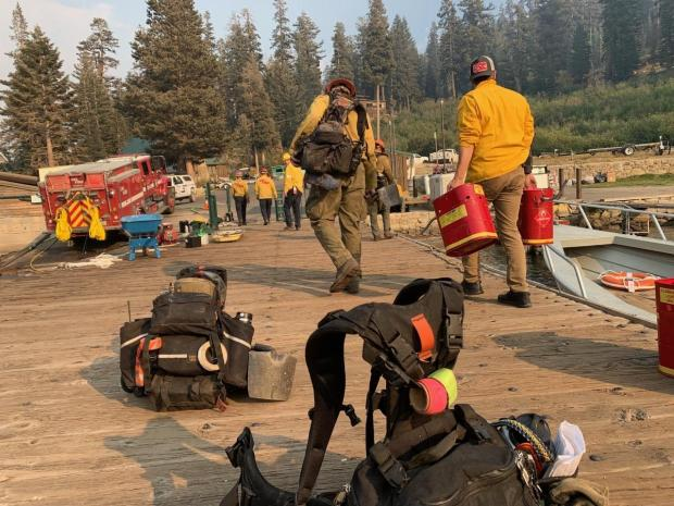 Firefighters walk on a boat dock with arms full of gas cans and equipment.