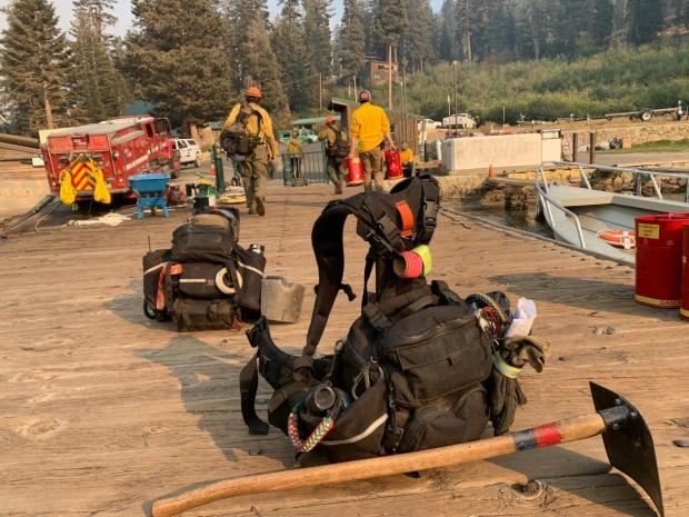 A handtool and fire pack sit on a dock with firefighters walking in the background.