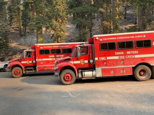 Two fire crew transport vehicles sit in a parking lot.