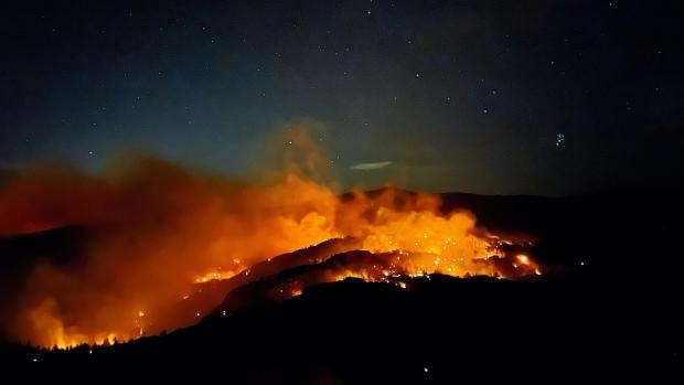 Bright orange flames light up a dark night sky while smoke is visible across a hilly landscape.