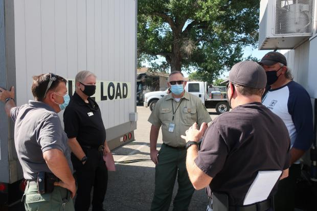 District Ranger and Incident Commander discuss operational issues while wearing masks