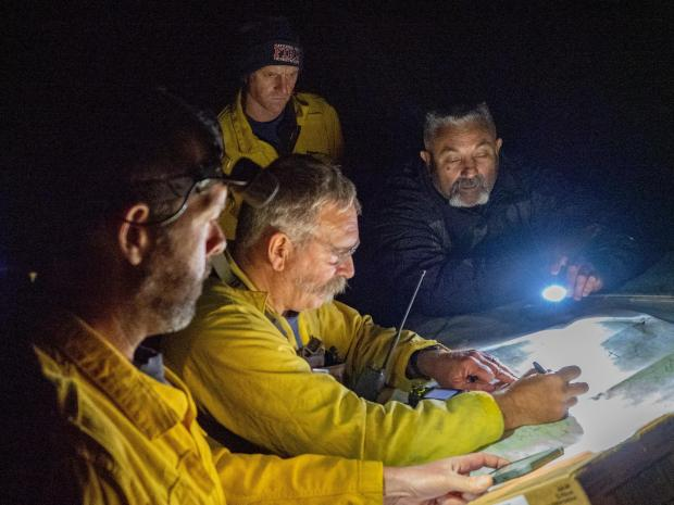 Four firefighters looking over map by flashlight