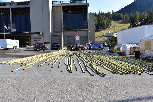 Lots of hoses laid flat on the ground in a line