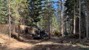 A chipper is on the road in the forest, chipping brush. The chips are falling to the forest floor. Several crew members in Nomex are seen to the side of the chipper.