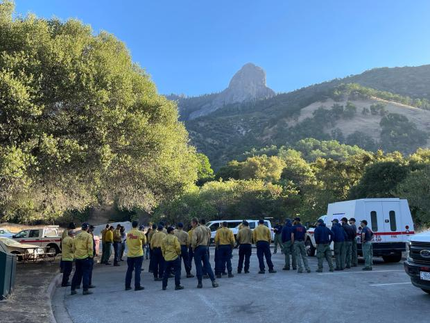 Firefighters gather in a circle in a parking lot with a large monolith peak in the distance.